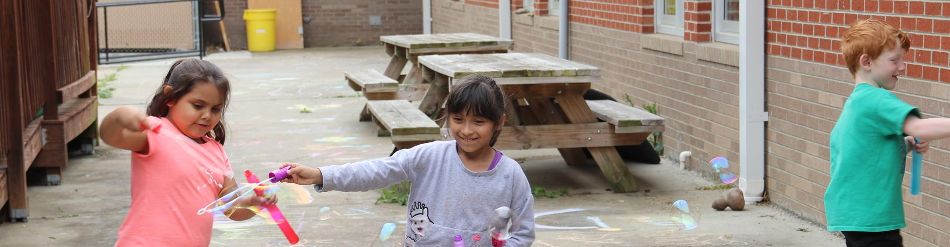 Three KWP students create bubbles with bubble wands.