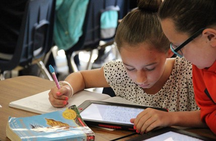 Two students using iPad and books