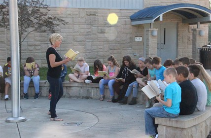 Teachering reading before a group of students, all holding books. Outside at flagpole.