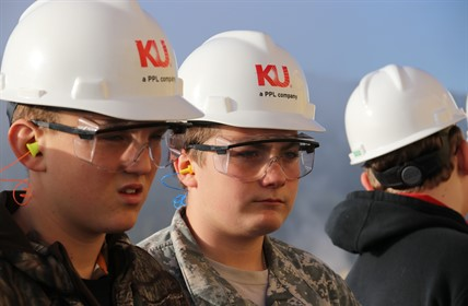 Two students wear KU hard hats and safety glasses.