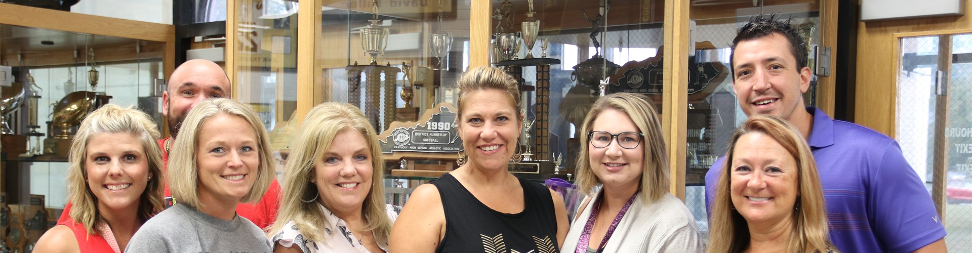 Eight staff members face the camera and smile in front  of the CCHS trophy case.